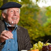old man wearing a beret holding a glass of wine